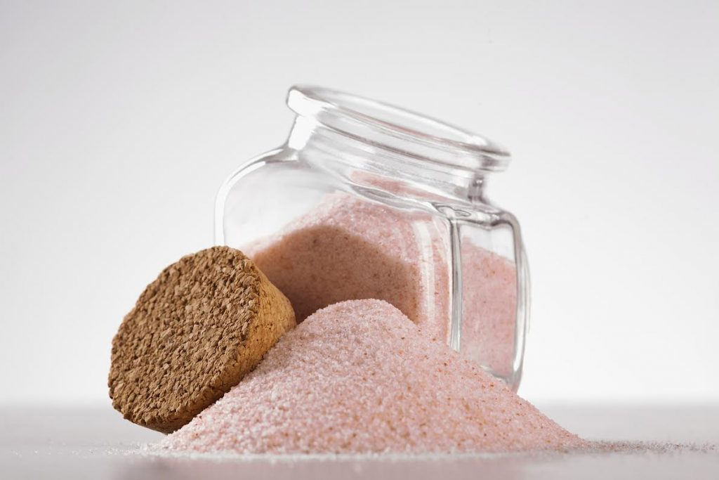 pink Himalayan salt in glass jar on white background