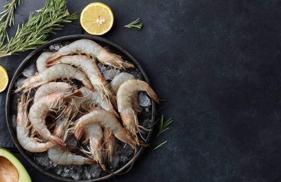Fresh tiger prawns in a plate with ice on black textured background, top view